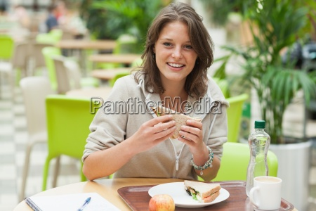 female student eating sandwich in the