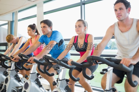 determined people working out at spinning