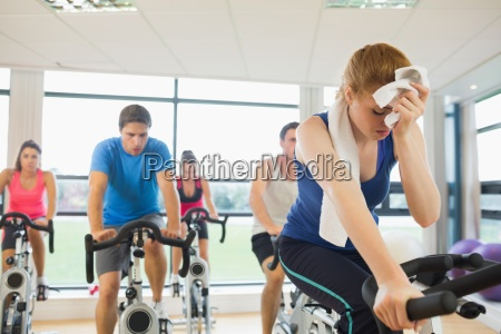 tired people working out at spinning