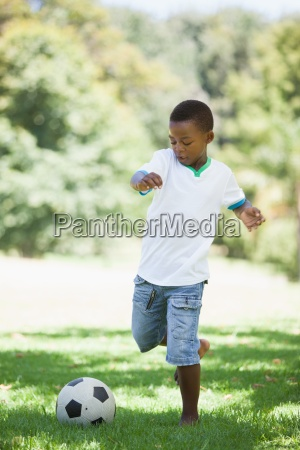 little boy kicking a football in