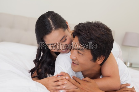 happy couple lying on bed together