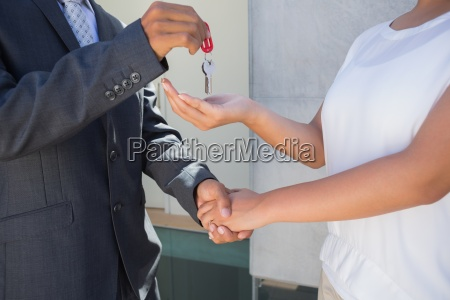 estate agent giving house key to