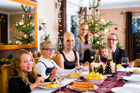family at christmas dinner sausages and