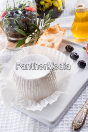 a soft cheese with spicy olives