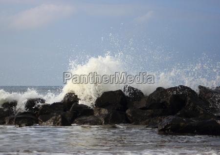 crashing waves against black rocks at