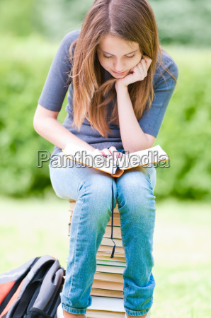 happy student girl sitting on pile