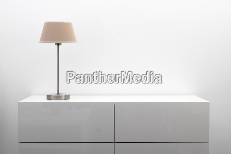 white commode with table lamp in