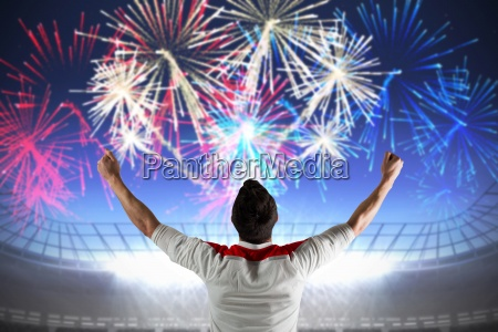 excited football fan cheering against fireworks