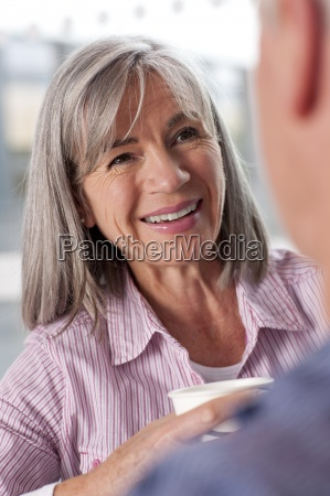 smiling senior woman drinking coffee and