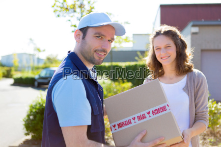 delivery, man, handing, over, a, parcel - 12879550