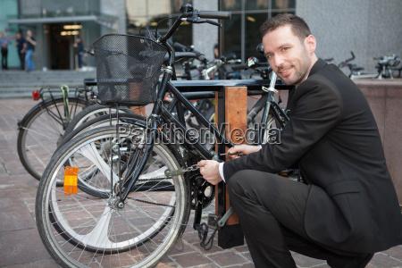 businessman unlock his bike after a