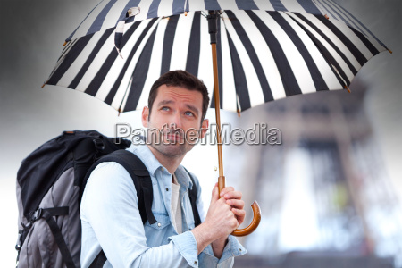 young attractive man suffering rain in