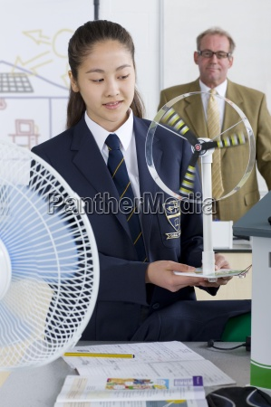 teacher in background watching female student