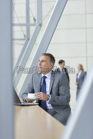 pensive businessman in suit drinking coffee