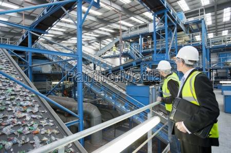businessmen watching plastic on conveyor belt