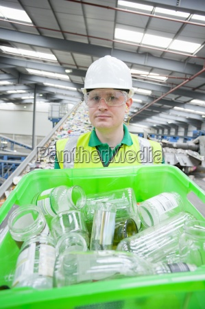 portrait of worker holding bin with
