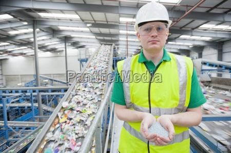 portrait of worker holding plastic pellets