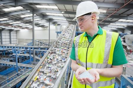 worker holding plastic pellets near conveyor