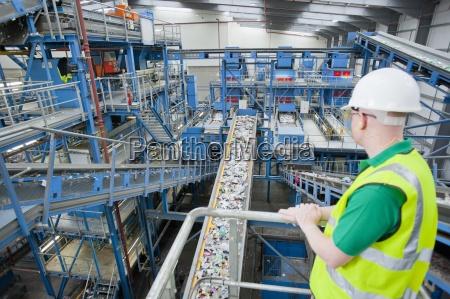 worker watching plastic on conveyor belt