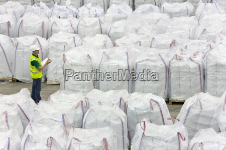 worker with clipboard among large bags