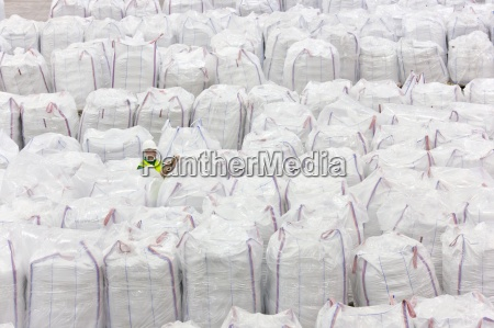 worker among large bags of plastic