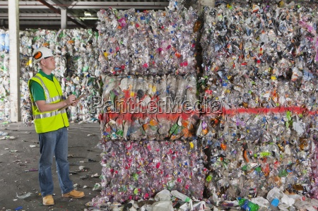 worker examining bales of recycled plastic