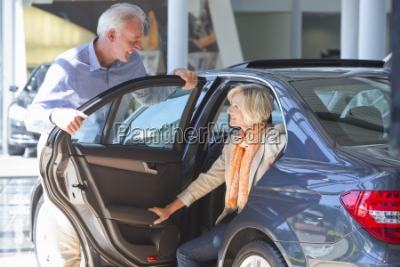 smiling couple looking at car in