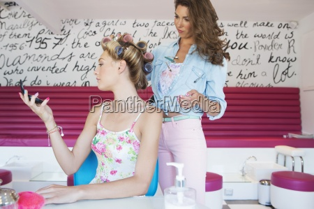 hairdresser checking curlers in womans hair