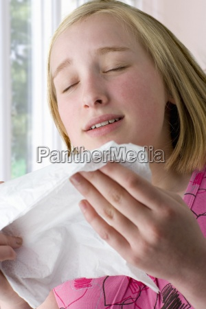 close up of girl sneezing into