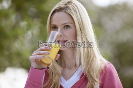 eine junge frau trinkt ein glas