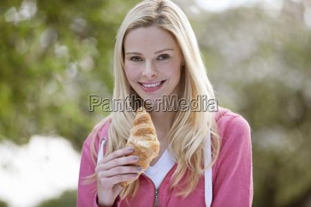 eine junge frau ein croissant essen