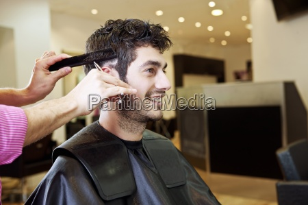 a male hairdresser cutting his male