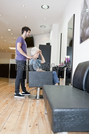 a male hairdresser discussing a female