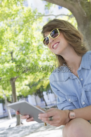 smiling young woman wearing sunglasses and