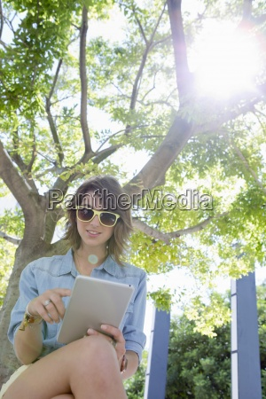 young woman wearing sunglasses and using