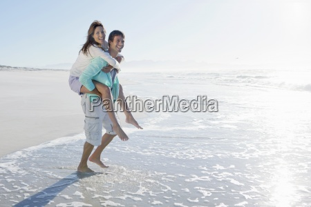 man piggybacking wife in surf on