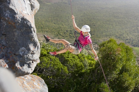 female rock climber abseiling down rock