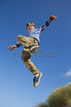 portrait of smiling boy jumping against