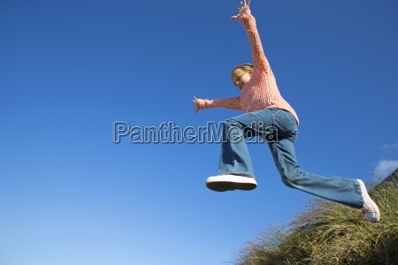 enthusiastic girl jumping against blue sky