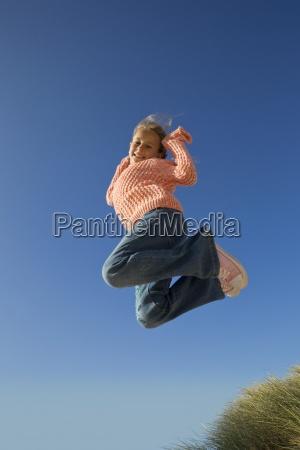portrait of smiling girl jumping against