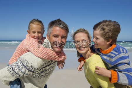 portrait of smiling parents piggybacking children