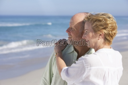 mature couple standing on beach embracing