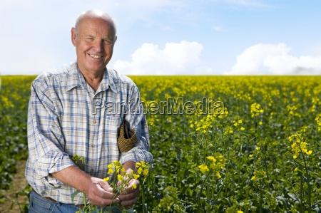 smiling farmer standing in sunny rape