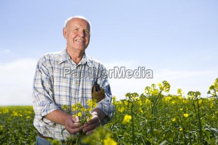 farmer standing in sunny rape seed