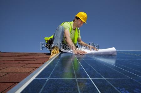 engineer examining blueprints on solar panel