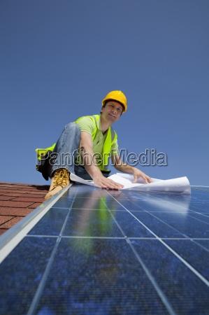 engineer holding blueprint on solar panel
