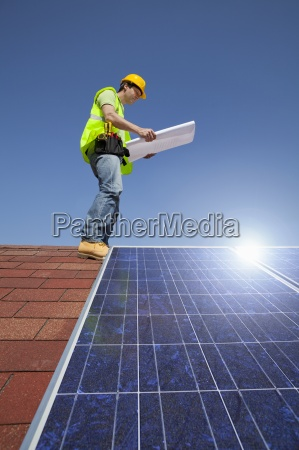 engineer examining blueprint on rooftop with