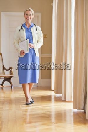 portrait of smiling home caregiver holding