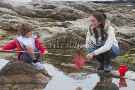 mother and son exploring rockpools together