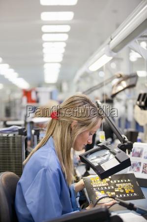 technician examining printed circuit board in
